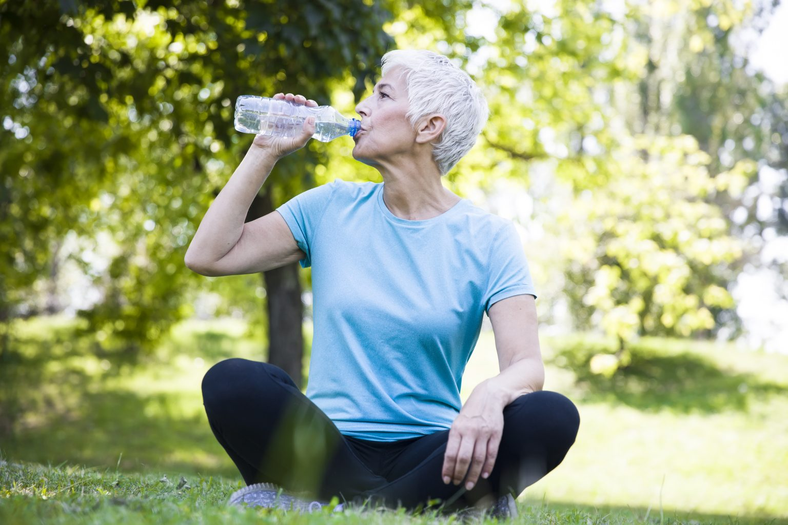 Senior woman sitting and drinking water after workout in park