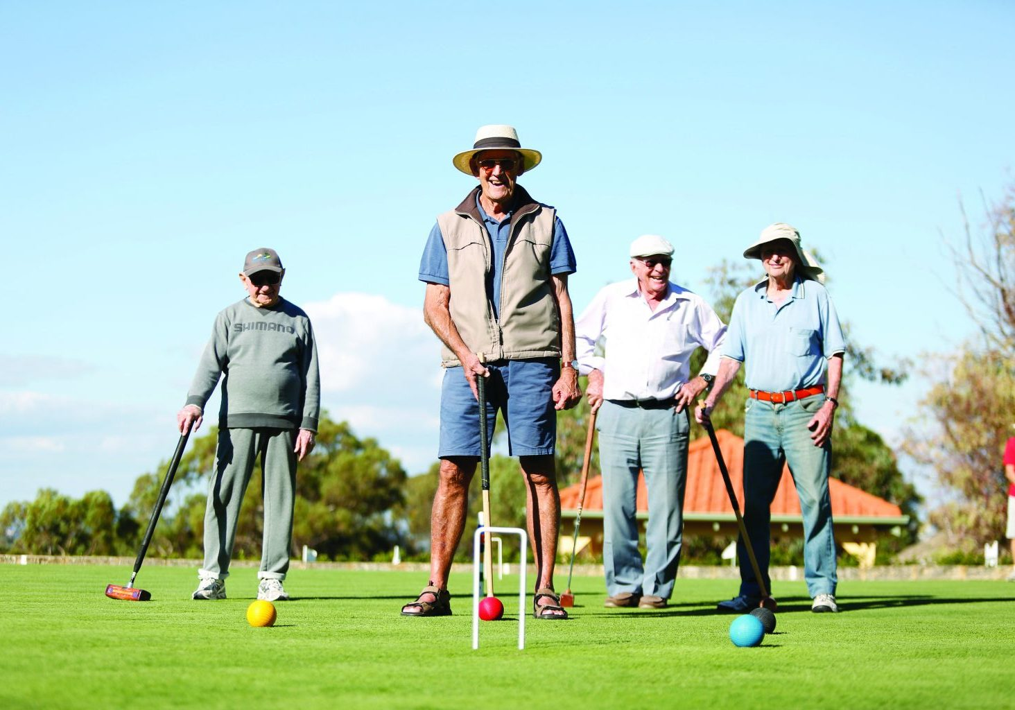 a group of men over 55 play lawn bowls for exercise.