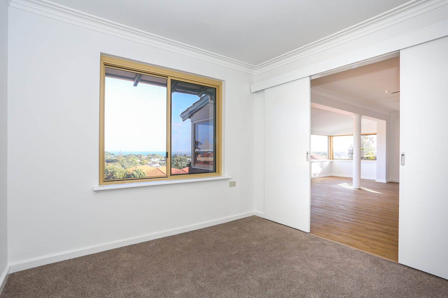 bedroom of villa for sale. window looks onto city beach and ocean views.
