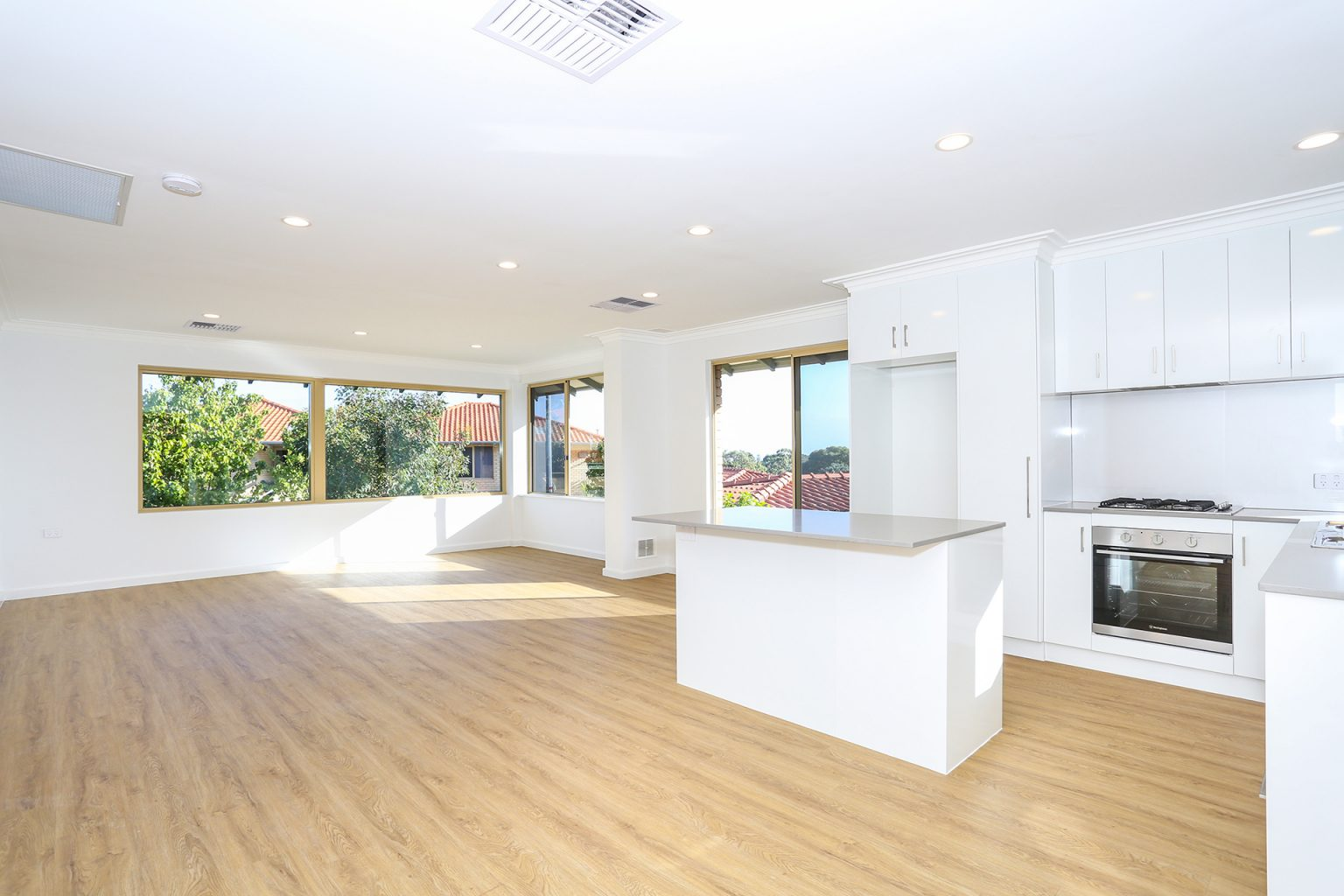 open plan living area of villa for sale with wooden floors, kitchen and large windows.